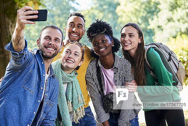 Glückliche Freunde machen ein Selfie mit ihrem Smartphone in einem öffentlichen Park