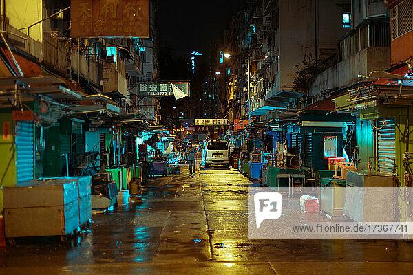 Blick auf eine Straße und einen geschlossenen Marktstand bei Nacht in Hongkong