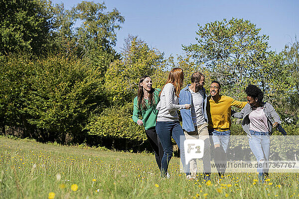 Glückliche junge Freunde haben Spaß beim gemeinsamen Spaziergang im Park Glückliche junge Freunde haben Spaß beim gemeinsamen Spaziergang im Park