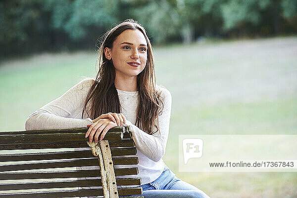 Smiling young woman sitting on bench in park Smiling young woman sitting on bench in park