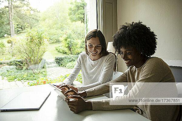 Lächelnde junge Frauen  die zu Hause ein digitales Tablet benutzen