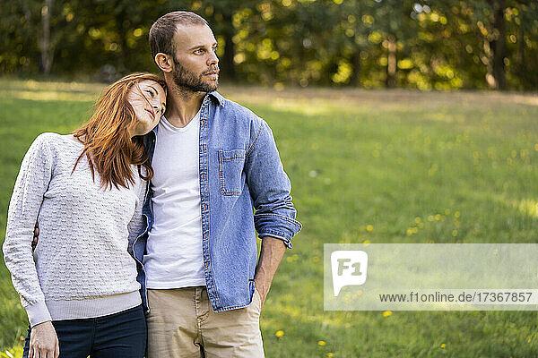 Lächelndes junges Paar bei einem Spaziergang in einem Park