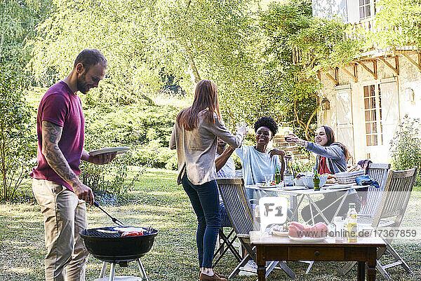 Junger Mann bereitet mit seinen Freunden am Tisch sitzend das Essen für den Grill vor Junger Mann bereitet mit seinen Freunden am Tisch sitzend das Essen für den Grill vor