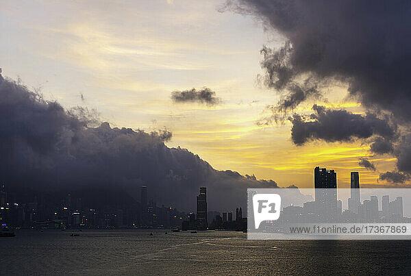 Blick auf die Skyline von Hongkong mit dem Victoria Harbour unter den Gewitterwolken in Hongkong  China