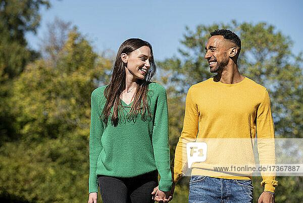 Lächelndes junges Paar beim Spaziergang in einem öffentlichen Park