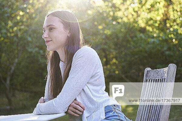 Lächelnde junge Frau sitzt auf einem Stuhl im Park
