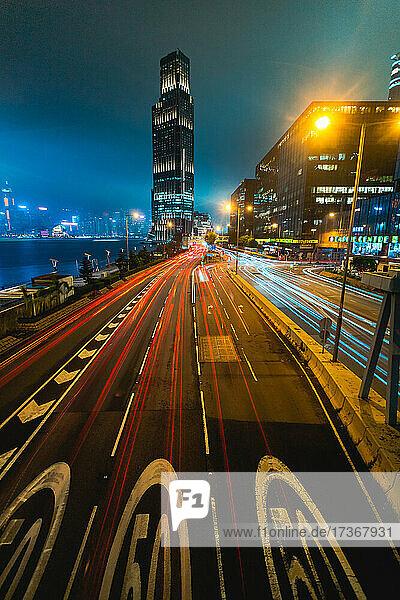 Langzeitbelichtung des fließenden Verkehrs auf der Straße mit modernen Gebäuden im Hintergrund  Hongkong