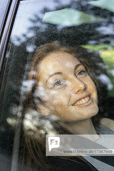 Lächelnde junge Frau im Auto sitzend Lächelnde junge Frau im Auto sitzend