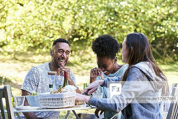Lächelnde junge Freunde beim Essen im Park