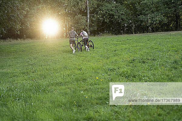 Junges Paar geht mit Fahrrädern im Wald spazieren Junges Paar geht mit Fahrrädern im Wald spazieren