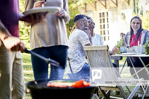 Young man preparing food in barbecue grill with his friends sitting at table in background Young man preparing food in barbecue grill with his friends sitting at table in background