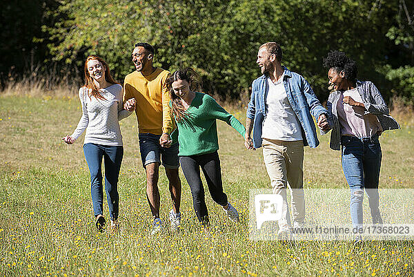 Glückliche junge Freunde  die zusammen in einem öffentlichen Park spazieren gehen