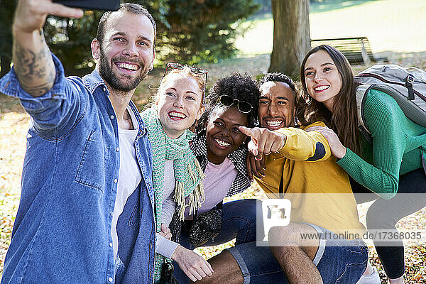 Smiling man taking selfie with smart phone while standing with friends in park Smiling man taking selfie with smart phone while standing with friends in park