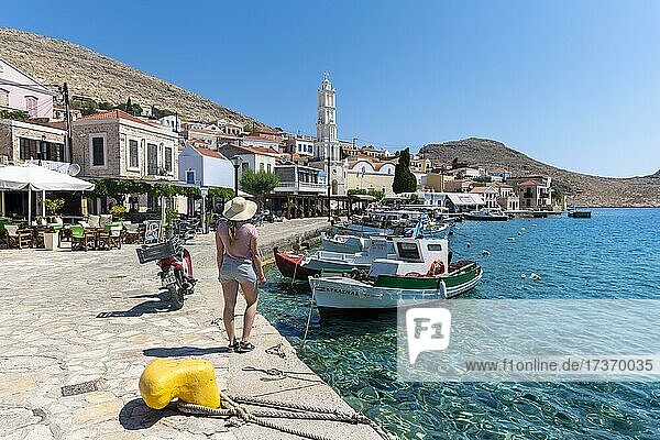 Tourist with sun hat  fishing boats in Halki harbour with turquoise water  promenade with colourful houses of Halki village  Halki  Dodecanese  Greece  Europe Tourist with sun hat, fishing boats in Halki harbour with turquoise water, promenade with colourful houses of Halki village, Halki, Dodecanese, Greece, Europe
