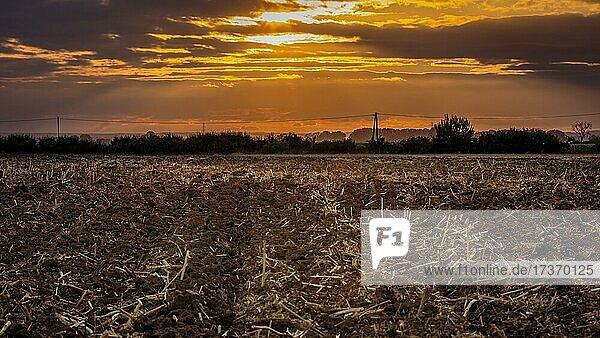 Plowed stubble  sunset  village in Poland Plowed stubble, sunset, village in Poland