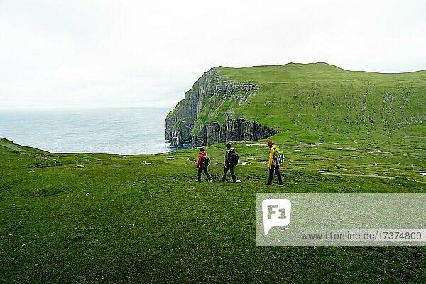 3 Hikers go to Ásmundarstakkur cliff  Sandvik  Suduroy  Faroe Islands  Europe