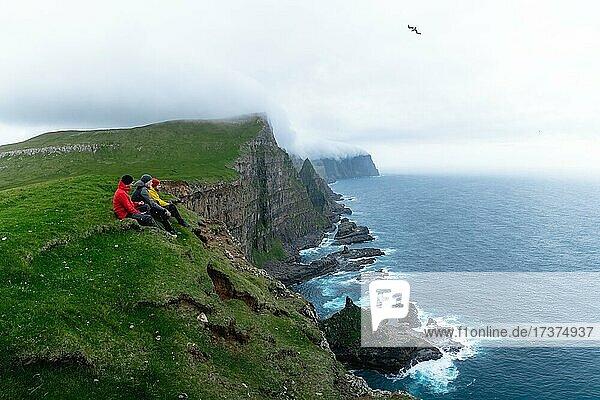 3 Walkers sitting overlooking Beinisforo Cliffs  Sandvik  Suduroy  Faroe Islands  Europe