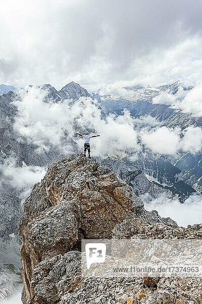 Hiker standing on a rock  at the summit of the Partenkirchner Dreitorspitze  view into the Reintal valley to cloudy peaks  in the background Zugspitzplatt and Zugspitze  Wetterstein Mountains  Garmisch Partenkirchen  Bavaria  Germany  Europe