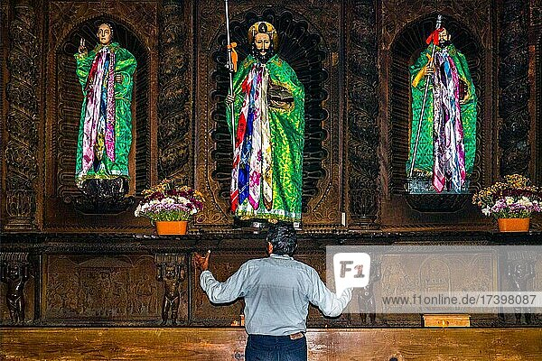 Shaman talking to wooden figures of the saints  dressed in traditional traditional costume  colonial-era Iglesia Parroquial Santiago Apostol of 1566  Santiago Atitlán  Lake Atitlán  Santiago Atitlán  Guatemala  Central America