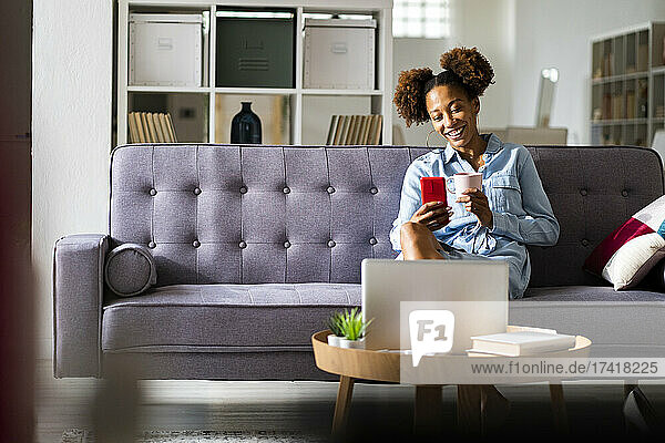 Young woman on video call through smart phone while having coffee in living room