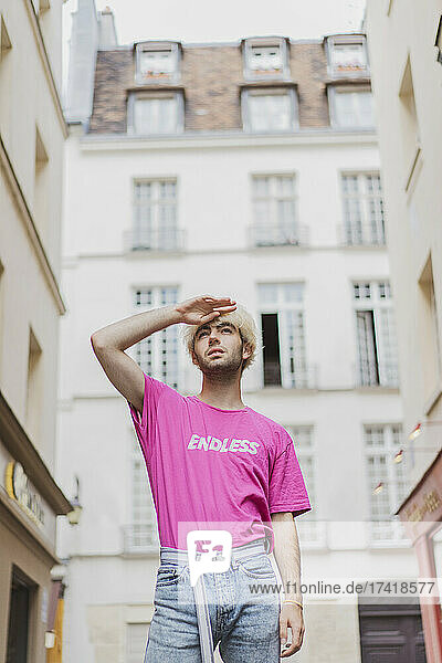 Young gay man wearing pink T-shirt shielding eyes in the city