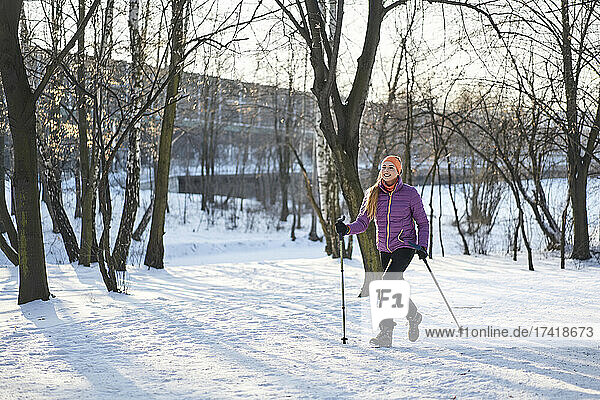 Woman with hiking pole walking on snow during winter