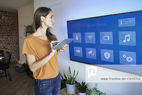 Woman looking at television while holding digital tablet at home