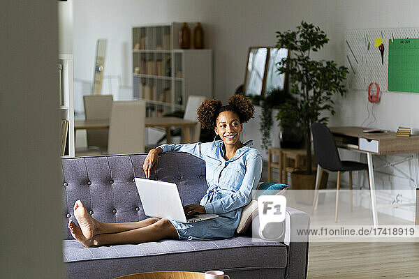 Smiling young woman sitting with laptop while looking away in living room
