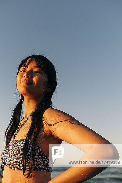 Beautiful young woman with bangs standing at beach