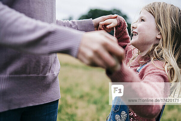 Smiling daughter holding hands of mother while playing outdoors