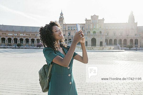 Smiling female tourist photographing through smart phone at Plaza De Espana  Seville  Spain