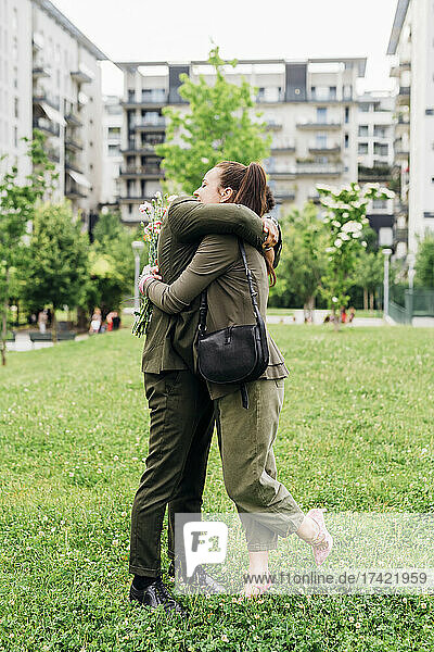 Business couple hugging each other while standing at park