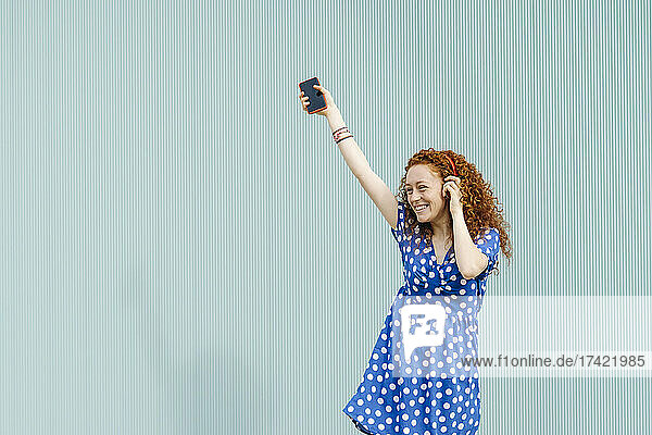 Cheerful woman listening music in front of blue wall