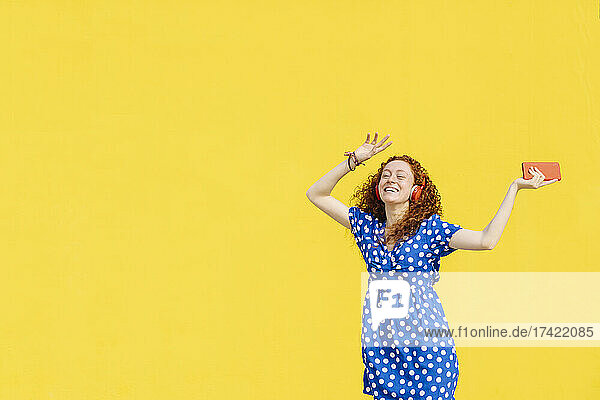 Cheerful woman dancing in front of yellow wall