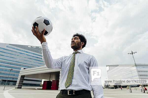 Businessman holding soccer ball while standing in city