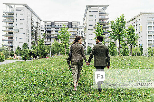 Business couple holding hands while walking on meadow