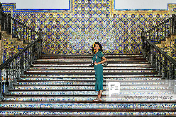 Female tourist looking away while standing on steps in Plaza De Espana  Seville  Spain
