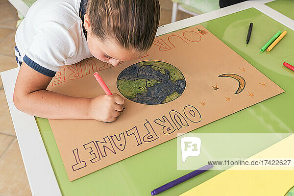 Girl drawing on cardboard paper at table in living room