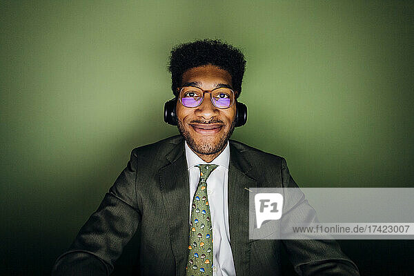 Smiling businessman with eyeglasses and wireless headphones in front of green wall