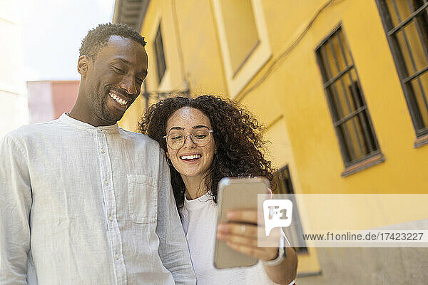 Smiling man looking at smart phone held by woman near building