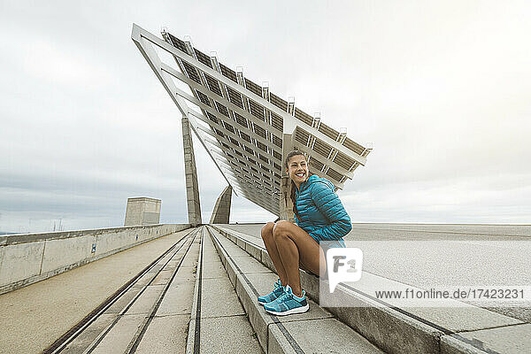 Smiling sportswoman looking away while sitting on steps