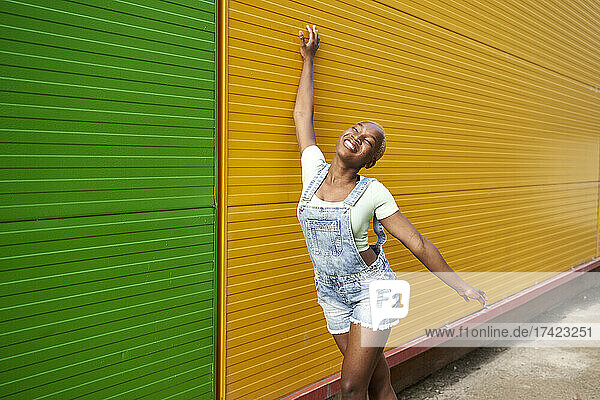 Smiling young woman with hand raised leaning on yellow wall