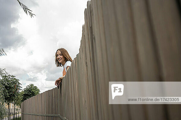 Young smiling woman leaning on retaining wall
