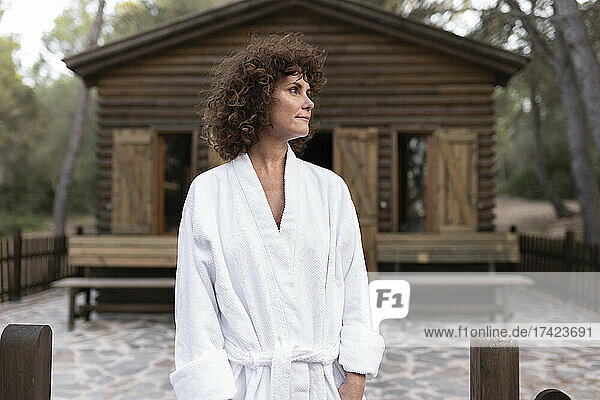 Woman wearing bathrobe standing in front of cabana