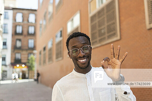 Smiling young man gesturing OK sign in front of buildings