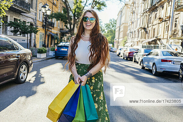 Cheerful young woman standing with shopping bags on street