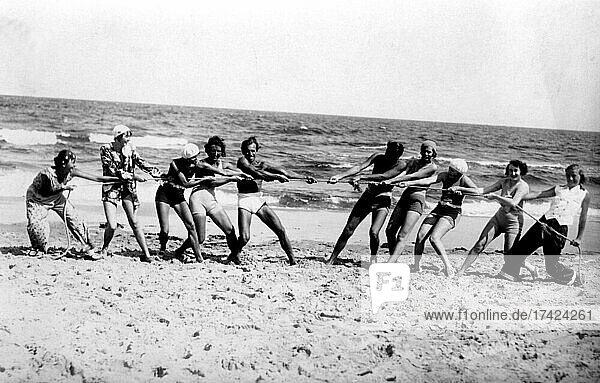 Group with bathers on the beach  funny  laughing  summer holidays  holiday  joie de vivre  rope pulling  competition  about 1930s  Baltic Sea  Usedom  Mecklenburg-Western Pomerania  Germany  Europe