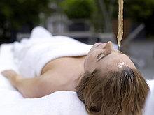 Junge Frau im Spa liegend mit Öl auf die Stirn gegossen, Augen geschlossen
