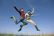junges paar in Latex Stiefel in die Luft springen
