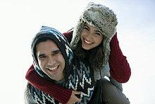 Paar in Winterkleidung spielen piggyback